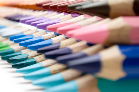 sharpen: Stacked colored pencils on a white background. Shallow depth of field.
