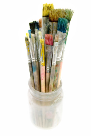 dipping: Bunch of dirty paintbrushes in a glass. Isolated on a white background.