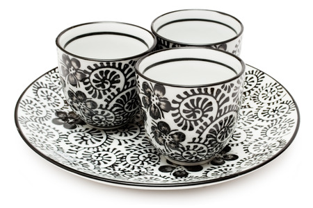 Three adorned cups on a plate isolated on a white background.