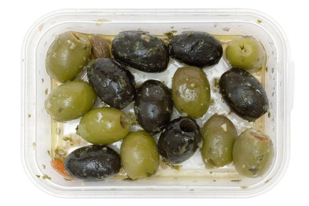 Black and green olives in a plastic bowl. Isolated on a white background. photo