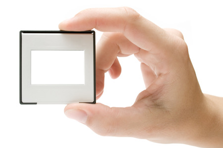 customisable: Female hand holding a plastic picture slide frame. Isolated on a white background.