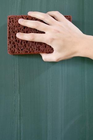 Female hand erasing a greenish chalkboard.