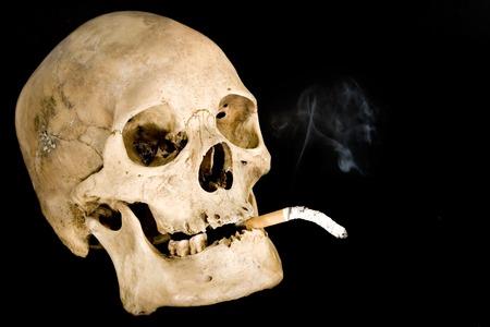 Human skull smoking. Isolated on a black background. photo