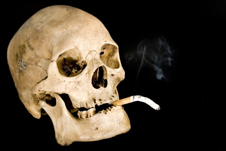 exitus: Human skull smoking. Isolated on a black background.