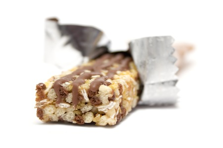 Wrapped healthy granola bar isolated on a white background. Фото со стока