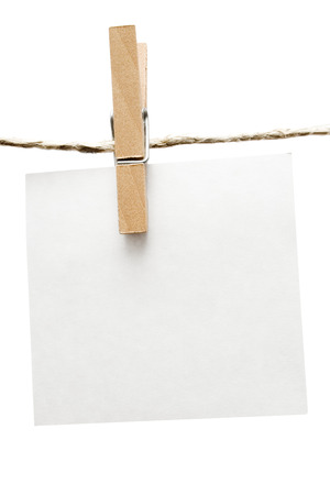 Blank note hanging on a clothesline. Isolated on a white background. Фото со стока
