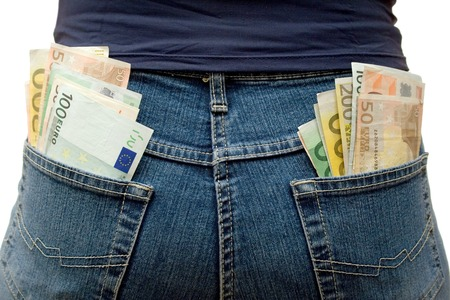provision: Blue jeans stuffed with Euro banknotes. White background. Stock Photo
