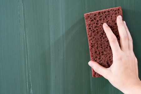 Female hand erasing a greenish blackboard. photo
