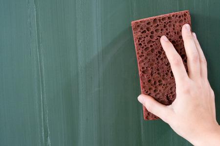 slate board: Female hand erasing a greenish blackboard.