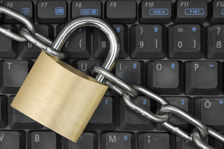 chainlinks: Padlock and chain locking a notebook keyboard.