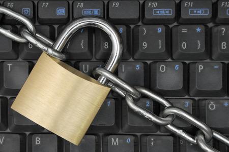 locking: Padlock and chain locking a notebook keyboard.