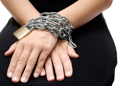 Woman in a black dress bound with chain and padlock. White background.