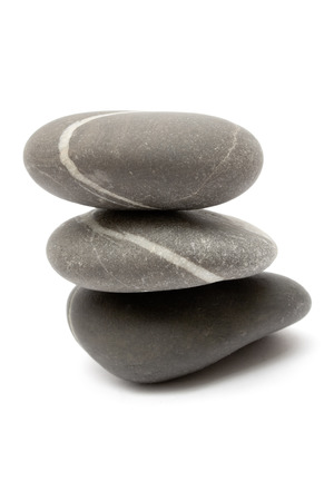 Three gray stones stacked on each other. Isolated on a white background. Stock Photo