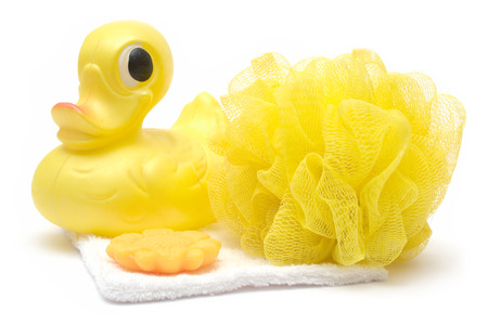 Rubber duck, sponge, soap and folded towel isolated on a white background. Фото со стока
