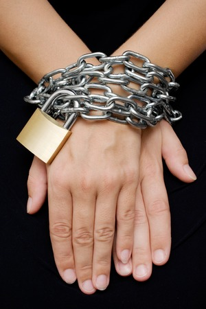 chainlinks: Female hands bound with chain and padlock. Isolated on a black background.