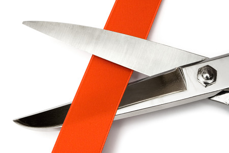 unveil: Close-up on scissors cutting a red satin ribbon. Isolated on a white background.