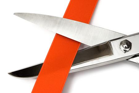 excise: Close-up sulle forbici tagliando un nastro di raso rosso. Isolata su uno sfondo bianco.