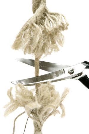 symbols  metaphors: Pair of scissors cutting a piece of rope. Isolated on a white background.