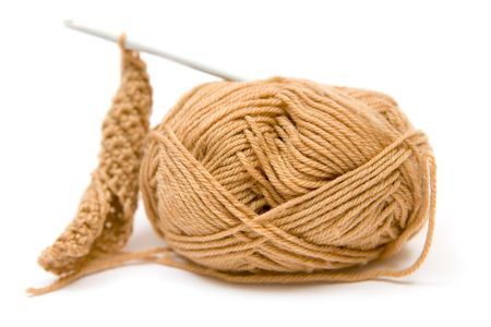 weave ball: Brown yarn and crotchet hook. White background.