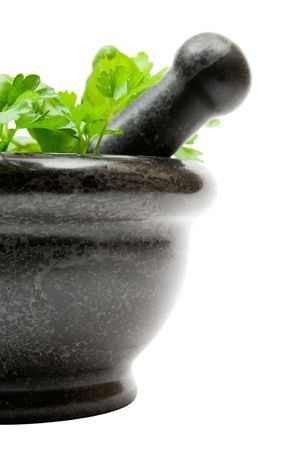 Crushing fresh herbs in a stone mortar. Isolated on a white background. photo
