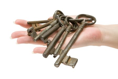 guarding: Female hand holding a rusty key ring. Isolated on a white background.