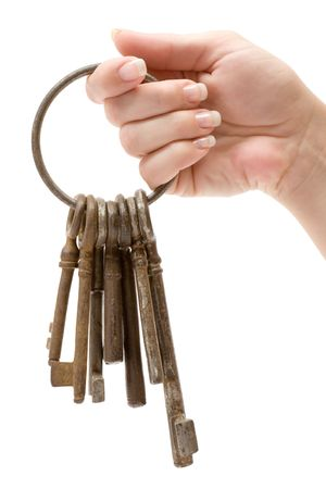 Female hand holding a bunch of old keys. Isolated on a white background. photo