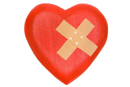 Wooden heart with a plaster. Isolated on a white background. photo