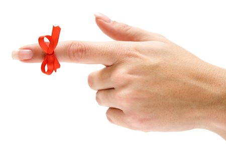 Finger with red bow pointing left. Isolated on a white background. Фото со стока