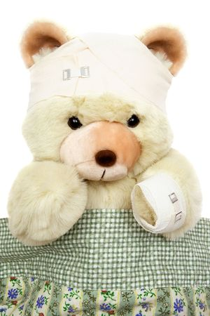 Bandaged teddy lying in bed. Isolated on a white background. photo