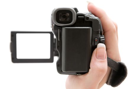 camcorder: Woman holding a small camcorder. Shallow depth of field. Focus on the back of the camera. Isolated on a white background. Stock Photo