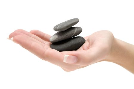 Female hand holding a stack of three dark stones. Isolated on a white background.