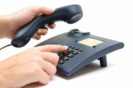 Dialing a number on a blue phone. White background. Фото со стока