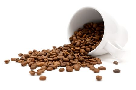 coffee spill: White cup and coffee beans. Shallow depth of field. White background.