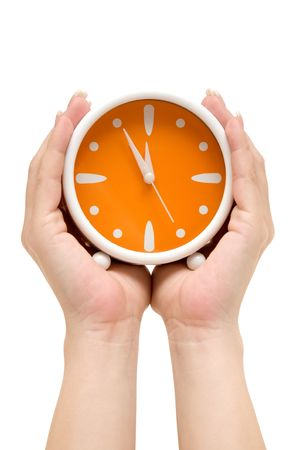Hands holding an orange alarm clock. Showing five minutes to midnight. Isolated on a white background.