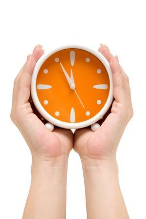 Manos celebración de una naranja despertador. Listado cinco minutos para la medianoche. Aislada en un fondo blanco.