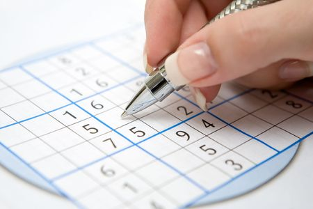 Female hand holding pen and doing a Sudoku game.
