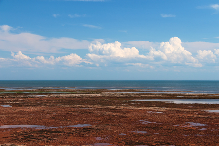 Red sand shore in Prince-Edward-Island at low tide with blue sky and white clouds