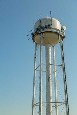 Water tower with dish and antennas for telecommunication on a blue sky