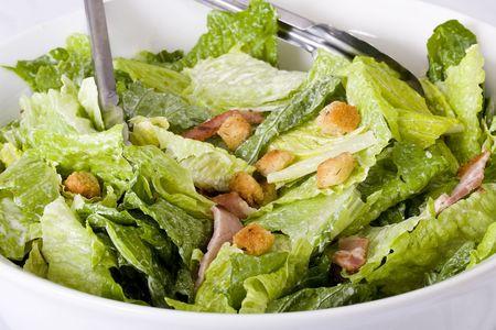ensalada cesar: Cerrar hasta ensalada Caesar con croutons caseros, rodajas de tocino, queso parmesano y aderezo C�sar en gran cuenco de cer�mica de color blanco.  Foto de archivo