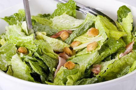 Close up Caesar salad with homemade croutons,  sliced bacon,  parmesan cheese and Caesar dressing in large ceramic white bowl. photo