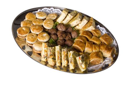 Platter of hot party pies, sausage rolls, quiche and savoury meatballs on a silver catering platter