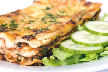 Close up of traditional beef lasagna with b�chamel sauce and fresh spinach. Side salad of gourmet lettuce and cucumbers. photo