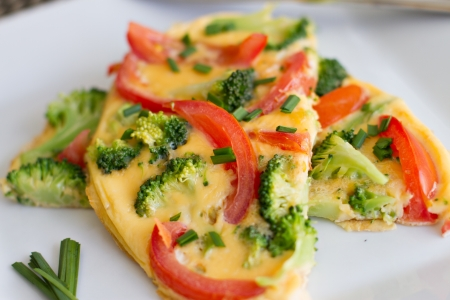 carb: Close up of healthy tomato and broccoli omelette (omelet) garnished with chives on a white plate.