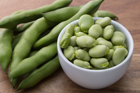 Close up fresh raw broad beans in a white bowl on a wooden cutting board surface Imagens