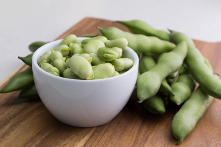 Close up fresh raw broad beans in a white bowl on a wooden cutting board surface Stok Fotoğraf