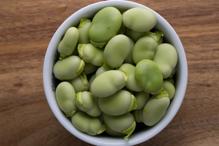 Close up fresh raw broad beans in a white bowl on a wooden cutting board surface Stock Photo