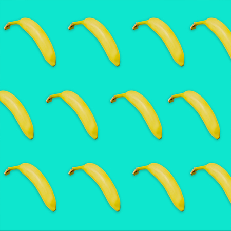 Yellow bananas pattern on turquoise colored background. Summer fruit conceptual image for covers, flyers, magazines.