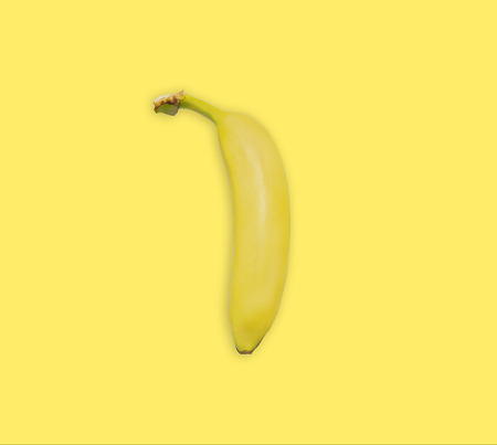 Yellow banana isolated on yellow background, top view. Minimalistic trendy image concept, bright summer color. Banana yellow summer background. Banque d'images