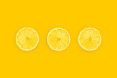 Fresh lemon slices on yellow background, top view. Summer bright background, citrus lemon fruit pieces, vitamin freshness concept.