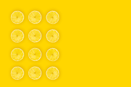 Fresh lemon slices on yellow background, top view. Summer bright background, lemon citrus fruit pieces set, vitamin freshness concept with space for text.